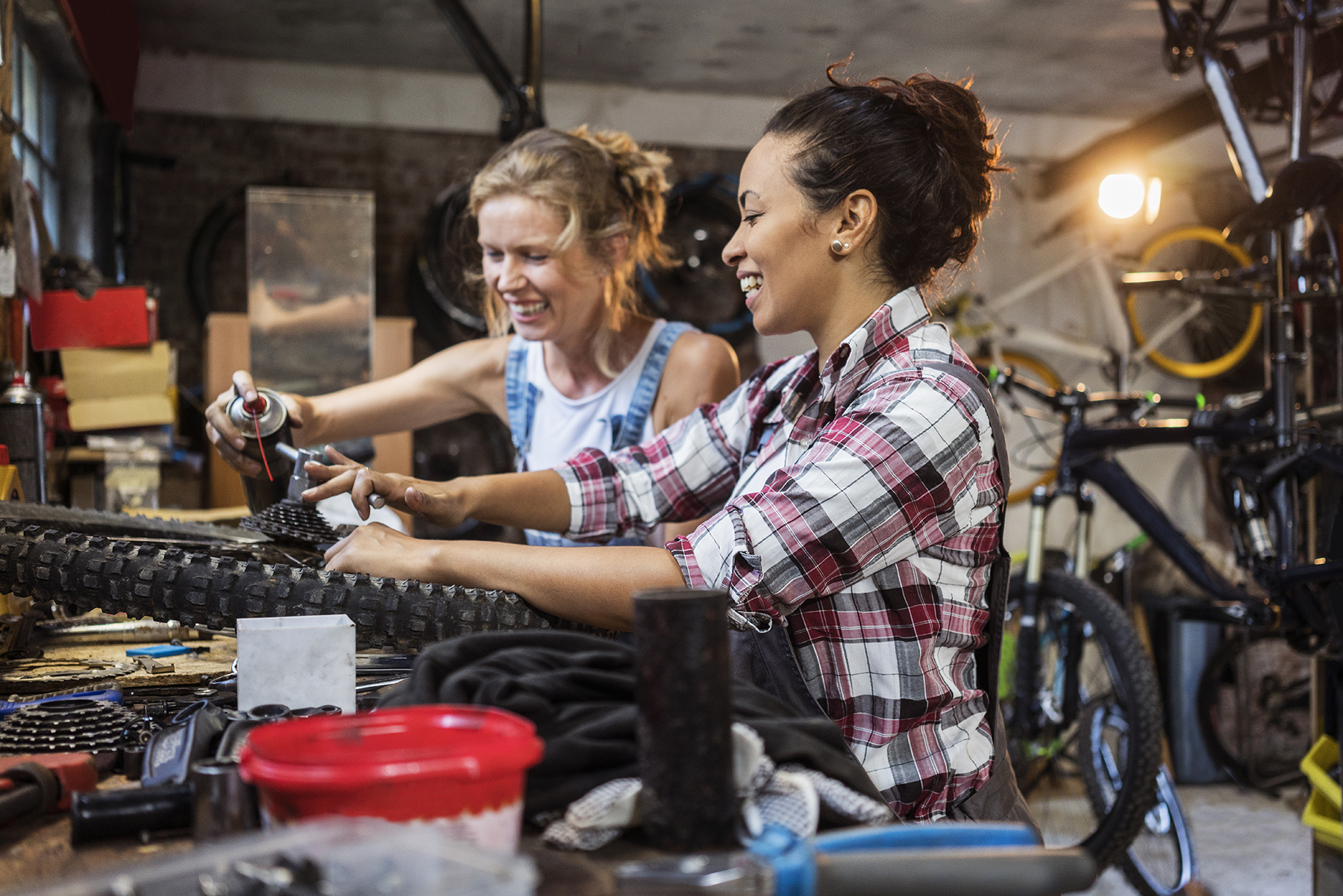Two women fixing bicycle's in their workshop