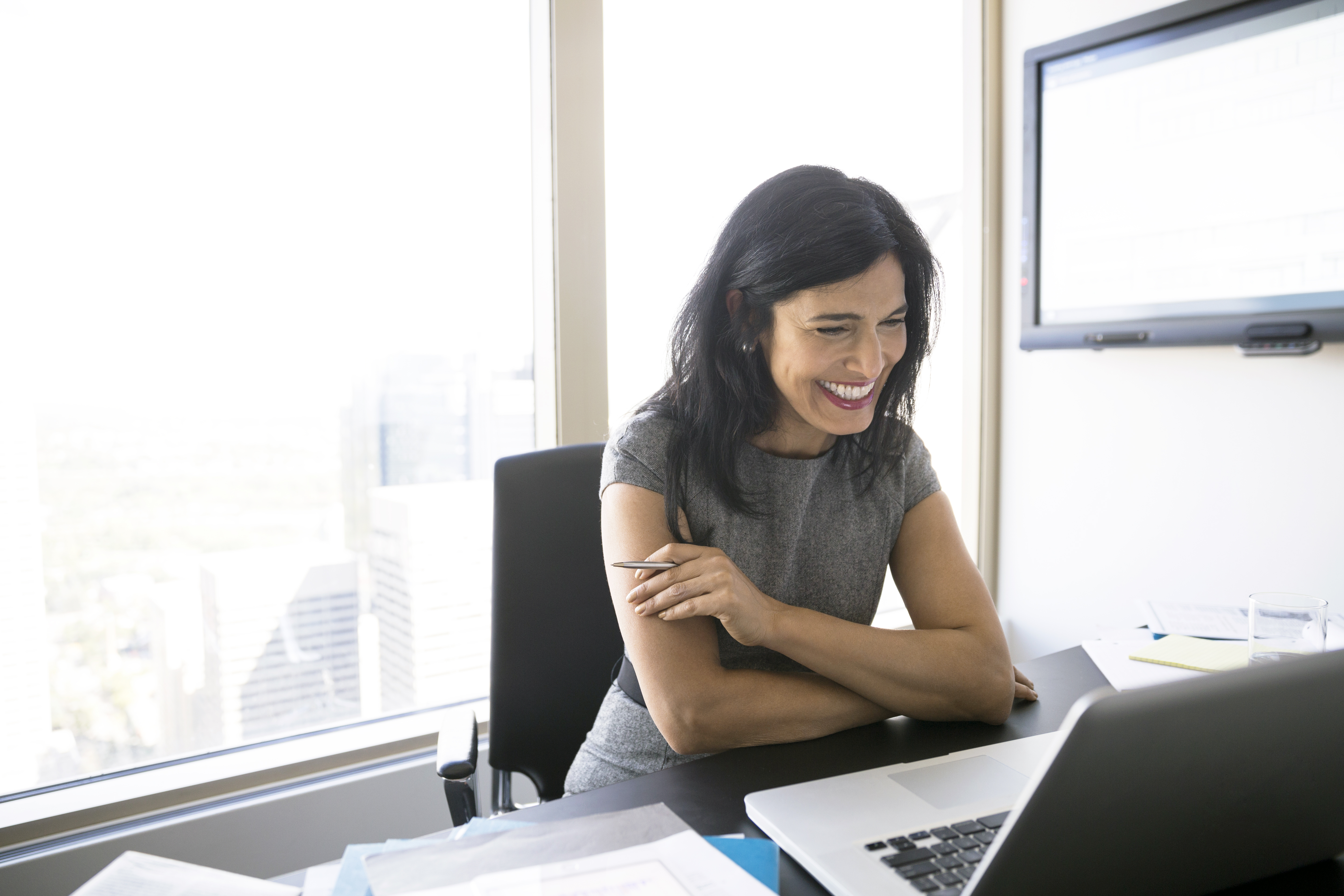Smiling woman video conferencing at laptop in conference room