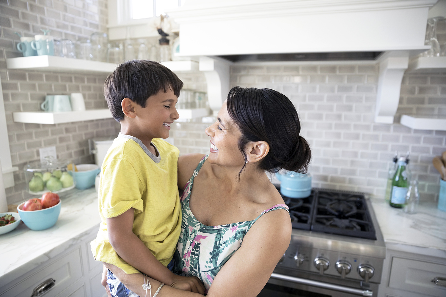 Smiling mother holding son in kitchen