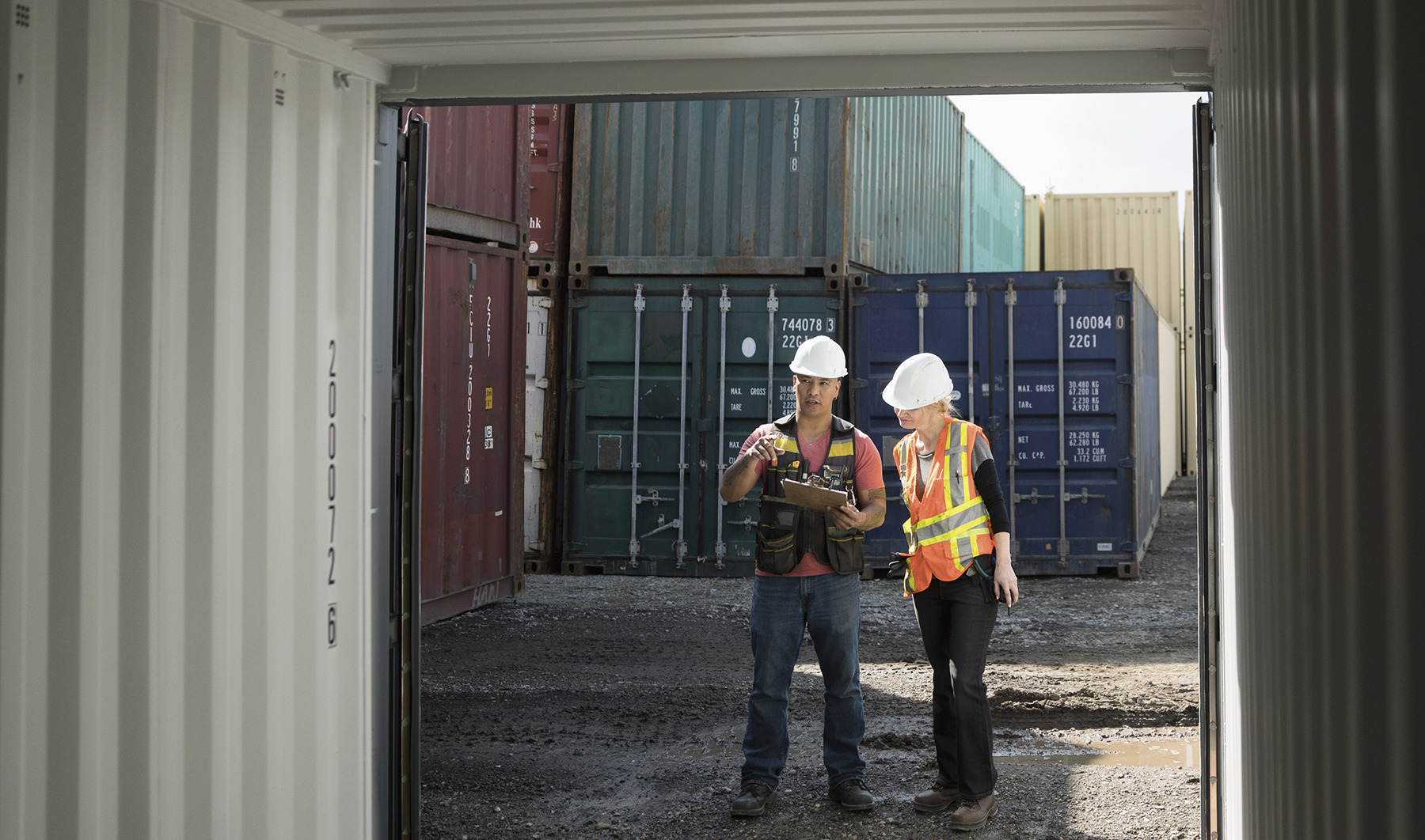 Workers inspecting empty shipping container in industrial container yard