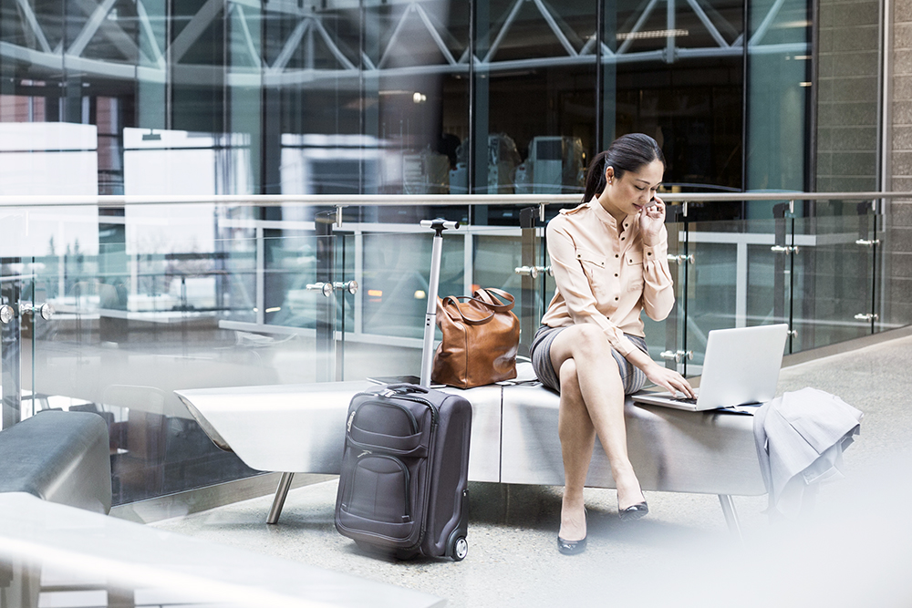 Businesswoman using laptop and cell phone in airport