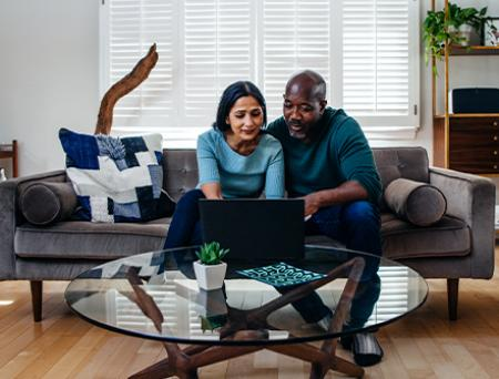 Mature married couple at home on the sofa looking at laptop