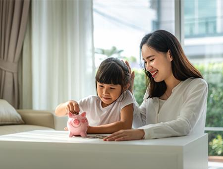 Happy mother and daughter saving money putting coins into piggy bank on table at home.