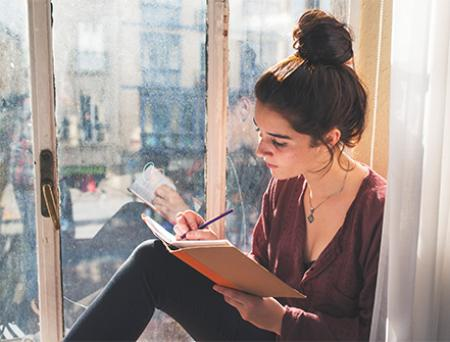 Young woman writes diary next to the window.