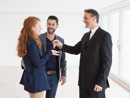 Estate agent handing over keys to young couple.